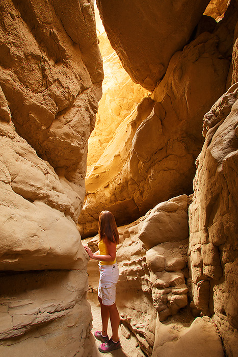 A visitor explores a slot canyon in Anza-Borrego Desert State Park, California. (model released)